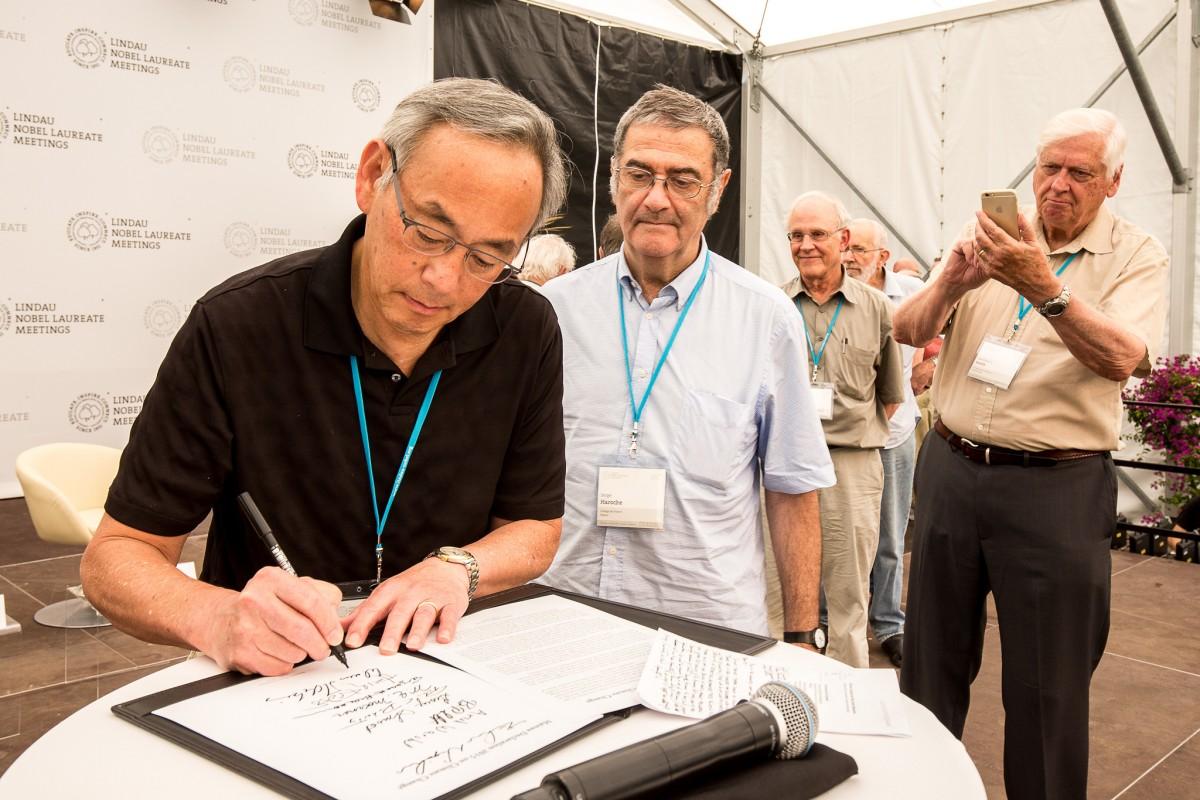 Steven Chu unterzeichnet die Mainau Declaration. Foto: Christian Flemming/Lindau Nobel Laureate Meetings